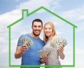 Smiling couple holding money over green house — Foto de Stock