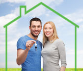 Smiling couple holding key over green house — Foto Stock