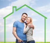Smiling couple hugging over green house — Foto Stock