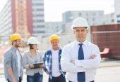 Grupa budowniczych uśmiechający się w hardhats na zewnątrz — Zdjęcie stockowe