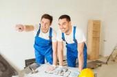 Constructeurs souriants avec blueprint — Photo