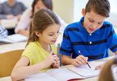 Groupe d'écoliers écrivant test en salle de classe — Photo