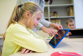 Dziewczynka z nauczycielem i tablet pc w szkole — Zdjęcie stockowe