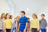 Group of smiling school kids walking in corridor — Stock Photo