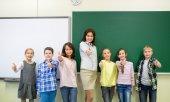 Groupe d'enfants d'âge scolaire et enseignant montrant les pouces vers le haut — Photo