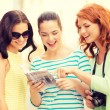 Smiling teenage girls with city guide and camera — Stock Photo #60675875