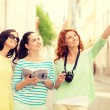 Smiling teenage girls with city guide and camera — Stock Photo #60675887