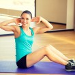 Smiling woman doing exercises on mat in gym — Stock Photo #60677081