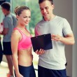 Smiling young woman with personal trainer in gym — Stock Photo #60677493