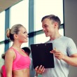 Smiling young woman with personal trainer in gym — Stock Photo #60677577