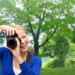 Smiling woman taking picture with digital camera — Stock Photo #60679531
