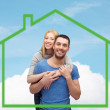 Smiling couple hugging over green house — Stock Photo #60679839