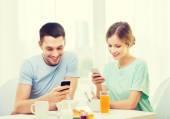 Souriant couple avec smartphones lisant news — Photo