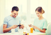 Smiling couple with smartphones taking picture — Stock Photo