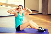 Lächelnde frau übungen auf matte in turnhalle — Stockfoto