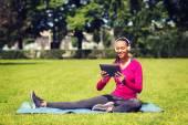 Lachende vrouw met tablet pc buitenshuis — Stockfoto