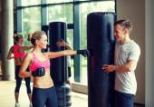 Lächelnde frau mit personal trainer im fitness-studio boxen — Stockfoto