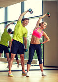 Smiling man and woman with dumbbells in gym — 图库照片