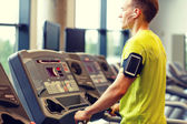 Homme avec smartphone exercice sur tapis roulant en salle de sport — Photo