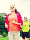 Sorrindo casal correndo ao ar livre — Foto Stock
