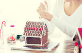 Close up of woman making gingerbread house at home — Fotografia Stock