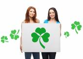 Smiling teenage girls holding board with shamrock — Foto Stock
