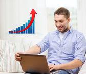 Homme souriant avec ordinateur portable et croissance dans le tableau à la maison — Photo