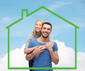Smiling couple hugging over green house — Foto de Stock