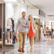 Happy young couple with shopping bags in mall — Stock Photo #60681073