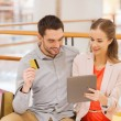 Couple with tablet pc and credit card in mall — Stock Photo #60681103