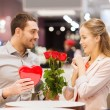 Happy couple with present and flowers in mall — Stock Photo #60681123