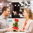 Happy couple with present and flowers in mall — Stock Photo #60681129