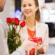 Happy couple with present and flowers in mall — Stock Photo #60681135