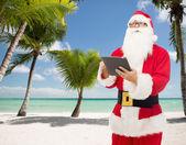 Человек в костюме Санта Клауса с Pc таблетки — Стоковое фото