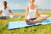 Close up of smiling couple making yoga exercises — Stock Photo