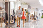 Happy young couple with shopping bags in mall — Stock Photo
