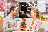 Happy couple with present and flowers in mall — Stock Photo