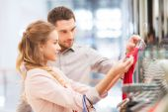 Счастливая молодая пара, выбирающая платье в торговом центре — Стоковое фото