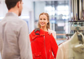 Happy young couple choosing clothes in mall — Stock Photo
