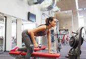Femme heureuse avec haltère flexion des muscles dans la salle de gym — Photo