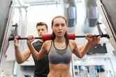 Man and woman with barbell flexing muscles in gym — 图库照片