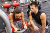 Young woman with trainer exercising on gym machine — Stock Photo