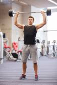 Young man flexing muscles with barbell in gym — Foto de Stock