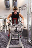 Young man exercising on t-bar row machine in gym — Stock Photo