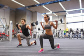 Young man and woman training with barbell in gym — Stock Photo