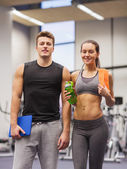 Happy couple in gym with water and tablet pc — 图库照片