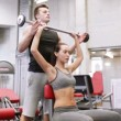 Man and woman with barbell flexing muscles in gym — Stock Video #60716799