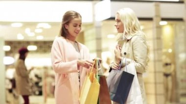 Happy young women with shopping bags in mall — Vídeo de Stock