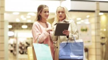 Happy young women with tablet pc and shopping bags — Stock Video