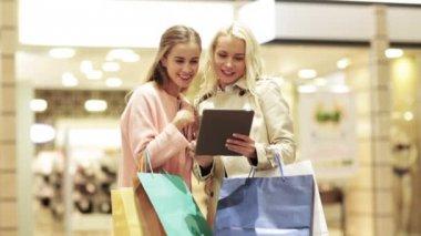 Glückliche junge Frauen mit Tabletpc und Einkaufstaschen — Stockvideo